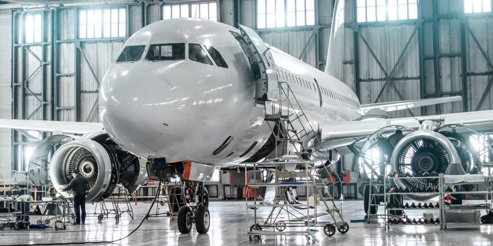 Passenger aircraft on maintenance of engine and fuselage repair in airport hangar